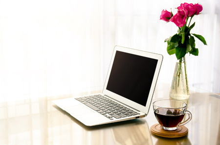 Computer notebook, Cup of Coffee and Rose in vase, Relaxing Home office workplace business woman with sun light.