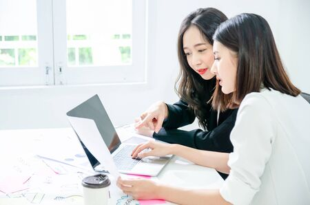 Photo for Two young asian women in office working and happy together on desktop. - Royalty Free Image