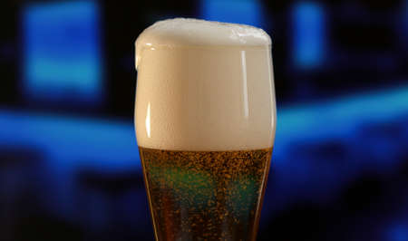 Close up shot of beer glass with drops and foam as a background