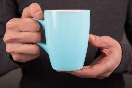 Photo pour A man in a gray shirt holding a blue mug - image libre de droit