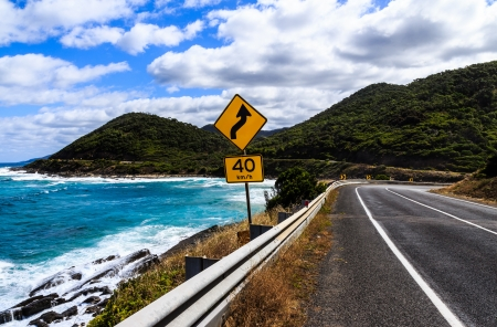 The yellow bend and 40 km h speed limit signs on the great ocean road in Victoria,Australia