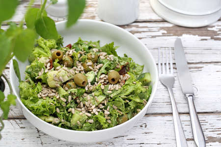 Green salad with olives, sun-dried tomatoes, sunflower seeds served with a sauce based on oil and herbs.
