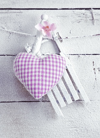 A pretty romantic checked violet needlework heart with flower hanging on painted white boards
