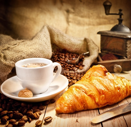 Coffee cup with a croissant and fresh coffee beanson a brown background