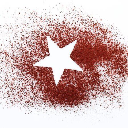 Crisp white star shape in the centre of randomly sprinkled cocoa or chocolate powder