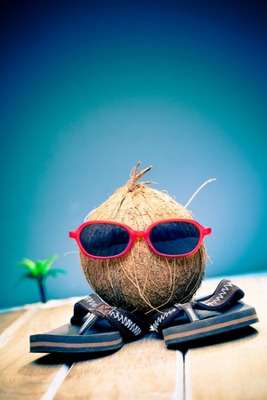 Humorous image of a coconut gent out sightseeing in his trendy red sunglasses on his summer vacation in the tropics