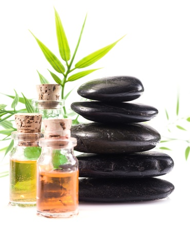 Massage oils and basalt stones necessary for a hot rock treatment in a spa setting