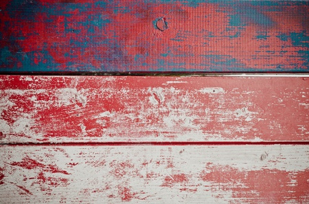 Grunge painted wooden texture background with red paint peeling off weathered timber planks with woodgrain