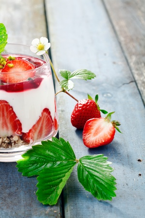 Strawberry Cream Pudding Dessert with cereals and yogurt on a blue wooden background for summer food concepts