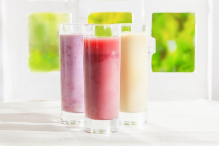 Variety of healthy fresh fruit t smoothies in glasses made from a blend of creamy yoghurt and liquidised fruit