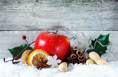 A delicious ripe red fresh apple with cinnamon spice and nuts in a snowy Christmas background against grey wooden boards with copyspace