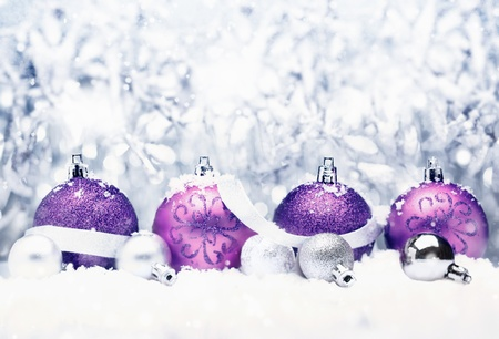 Decorative Christmas greeting with pretty purple baubles with festive silver bow and bokeh
