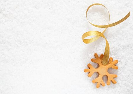 Crisp fresh Christmas snowflake biscuit with a decorative gold ribbon on a background of fresh snow with copyspace for your greetings
