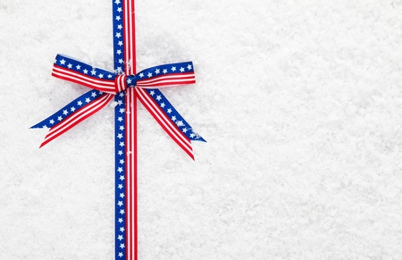 Decorative patriotic American ribbon and bow with the stars and stripes on winter snow for your Christmas greeting