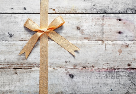 Decorative golden bow and ribbon on old rustic wooden boards with woodgrain copyspace for your Christmas, birthday or anniversary message