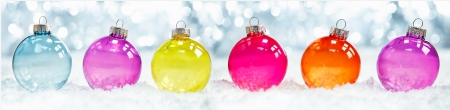 Foto de Colourful translucent Christmas baubles arranged in a row in snow against sparkling party ligts suitable as a banner or border - Imagen libre de derechos