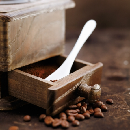 Freshly ground coffee and a measuring spoon in the open drawer of an old retro wooden grinder
