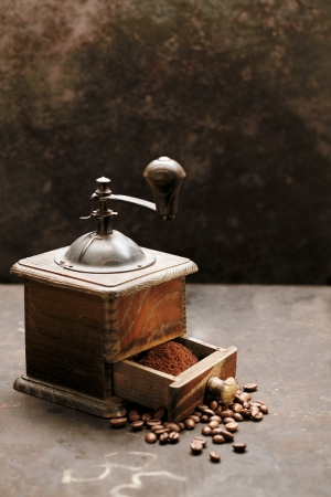 Old rustic wooden coffee grinder on a slate surface with scattered roasted coffee beans and freshly ground powder in the drawer ready to be used for filter coffee, espresso or cappuccino