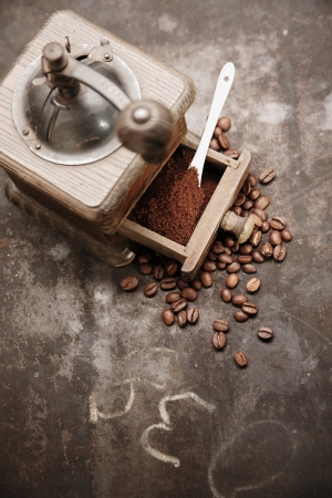 Overhead view of an old manual wooden coffee grinder with an open drawer filled with freshly ground coffee surrounded by scattered coffee beans on a grungy chalkboard with copyspace