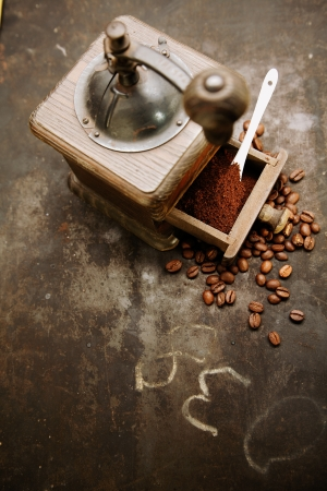 Overhead view of an old manual rustic wooden coffee grinder with an open drawer filled with freshly ground coffee with scattered roasted coffee beans on a grungy slate with scribblings and copyspace