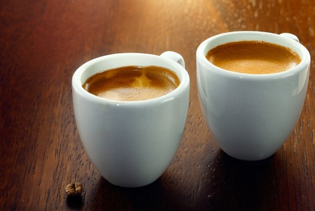 Two espresso coffees in small white cups,with a single coffee bean resting on the wood background