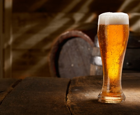 Closeup of a glass of fresh foamy beer on a table in a vintage beer cellar