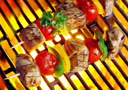 Closeup of two delicious meat kebabs skewered with peppers and tomato sizzling over the coals of a barbecue