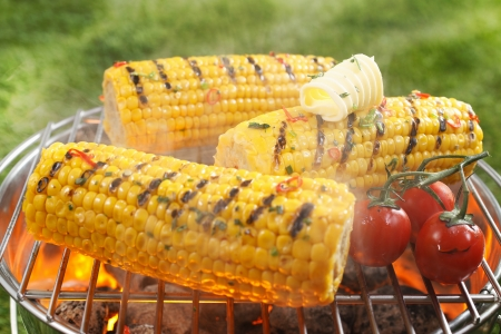 Foto für Healthy vegetarian barbecue with ripe golden corn on the cob and juicy red cherry tomatoes grilling over the fire outdoors on a green lawn - Lizenzfreies Bild