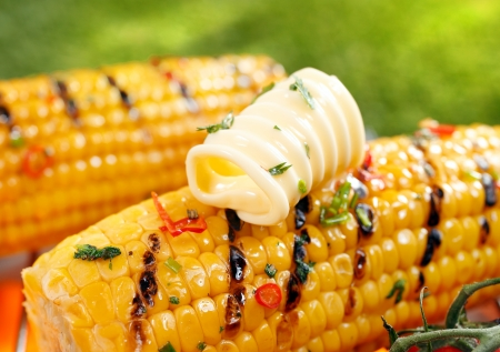 Foto für Delicious golden grilled corn on the cob served outdoors with a curl of fresh farm butter - Lizenzfreies Bild