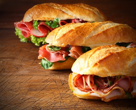 Assorted delicious baguette sandwiches filled with thinly sliced ham or salami and fresh green lettuce or basil arranged in an oblique row on an old wooden table with copyspace