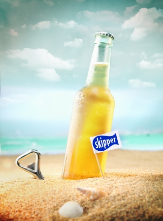 Capped bottle of chilled fruity orange soda or ale (beer) standing in the golden sand on a tropical beach with a bottle opener and Skipper sign. Look at my portfolio for more cocktails.
