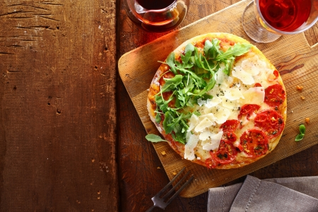 Patriotic Italian tricolore pizza with stripes of red, white and green in the colours of the national flag formed by tomato, cheese and fresh rocket leaves used for the topping on a wooden table with copyspace