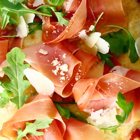 Delicious thinly sliced Italian prosciutto ham and fresh rocket leaves served as a topping on a pizza base, closeup view