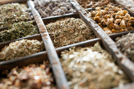 Assorted dried herbs in a printers tray with focus to chamomile flowers and a blend of mixed herbs for use in the kitchen to season and flavour food