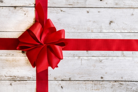 Colourful red Christmas ribbon tied with an ornamental bow on weathered white painted wood with copyspace for your seasonal greeting