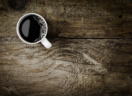 Overhead view of a freshly brewed mug of espresso coffee on rustic wooden background with woodgrain texture and cracks, with copyspace