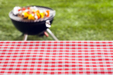 Empty picnic table background covered in a fresh country red and white checked cloth for your product placement or advertising with a barbecue on a green lawn behind