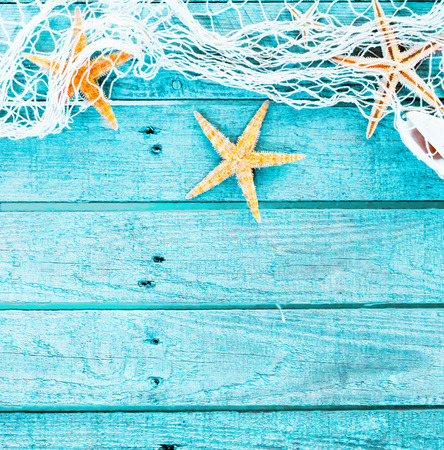 Pretty turquoise blue nautical background decorated with draped fishing net and starfish on painted rustic wooden boards with copyspace suitable as a card or party invitation, square format