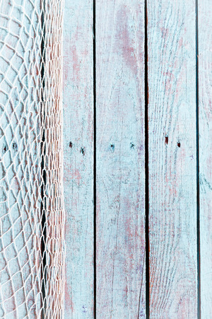 Fishing net former a vertical border on the left of old rustic blue painted weathered wooden boards with copyspace in a marine background