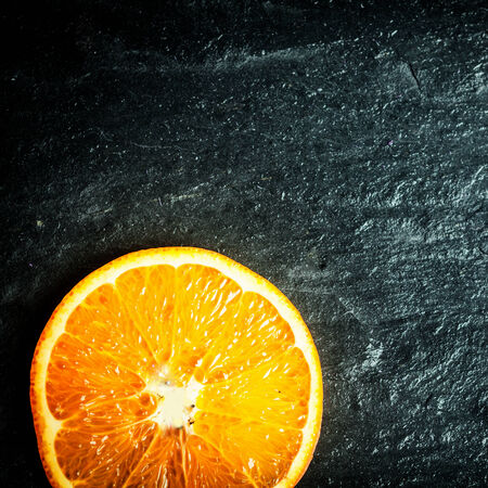 Colorful halved fresh juicy ripe orange on a dark texture wooden surface with copyspace, overhead view in square format