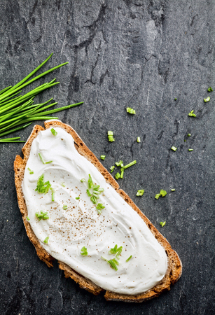 Cream cheese topping with chopped chives on a slice of healthy rye bread viewed from above with fresh chives on a dark textured background with copyspace