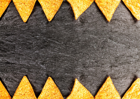 Border of golden crisp nachos or corn tortillas arrange top and bottom in a geometric pattern in horizontal format on textured slate with copyspace