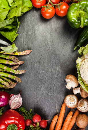 Frame or border of assorted farm fresh vegetables on slate with copyspace including carrots, asparagus, tomato, pepper, carrots , mushroom and radishの写真素材