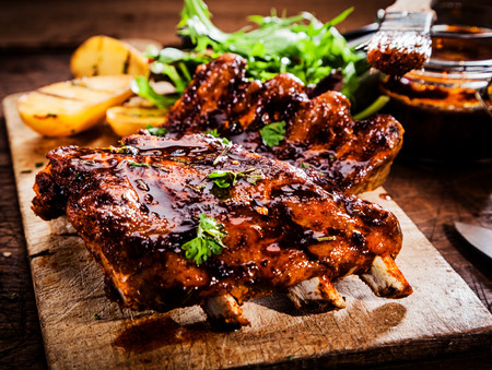 Photo pour Delicious barbecued ribs seasoned with a spicy basting sauce and served with chopped fresh herbs on an old rustic wooden chopping board in a country kitchen - image libre de droit
