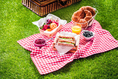 Healthy picnic for a summer vacation with freshly baked croissants, fresh fruit and fruit salad, sandwiches and a glass of refreshing orange juice laid out on a red and white checked cloth and hamper