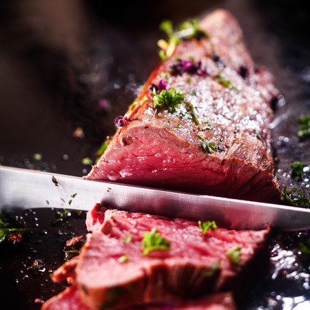 Photo pour Carving a portion of delicious rare roast beef sirloin of fillet seasoned with fresh herbs with a large steel carving knife - image libre de droit