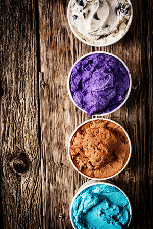 Gourmet selection of ice cream or frozen yoghurt in a variety of colours and flavours served on a rustic wooden table in a row of plastic takeaway tubs with copyspace