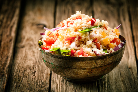 Heaped rustic bowl of savory quinoa with herbs, peppers and tomato for a healthy vegetarian dish rich in protein and nutrients standing on old wooden boards