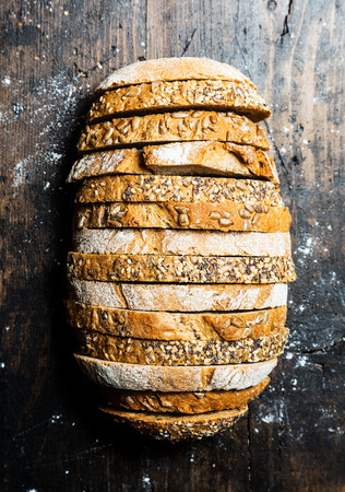 Interesting loaf of bread made up of alternate slices of brown wholewheat bread with seeds on the crust and rye bread viewed from above on an old wood surface