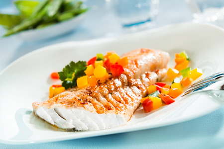 Foto de Delicious healthy grilled fish fillet served on a platter with a colorful fresh salad for a tasty seafood dinner - Imagen libre de derechos